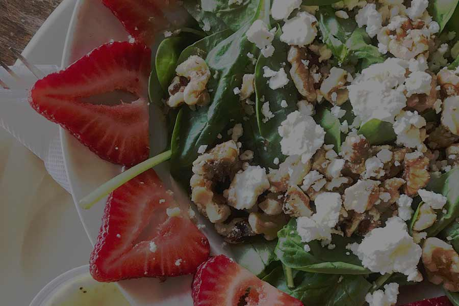 A Sweet & Tangy salad with strawberries, spinach, goat cheese, and walnuts.