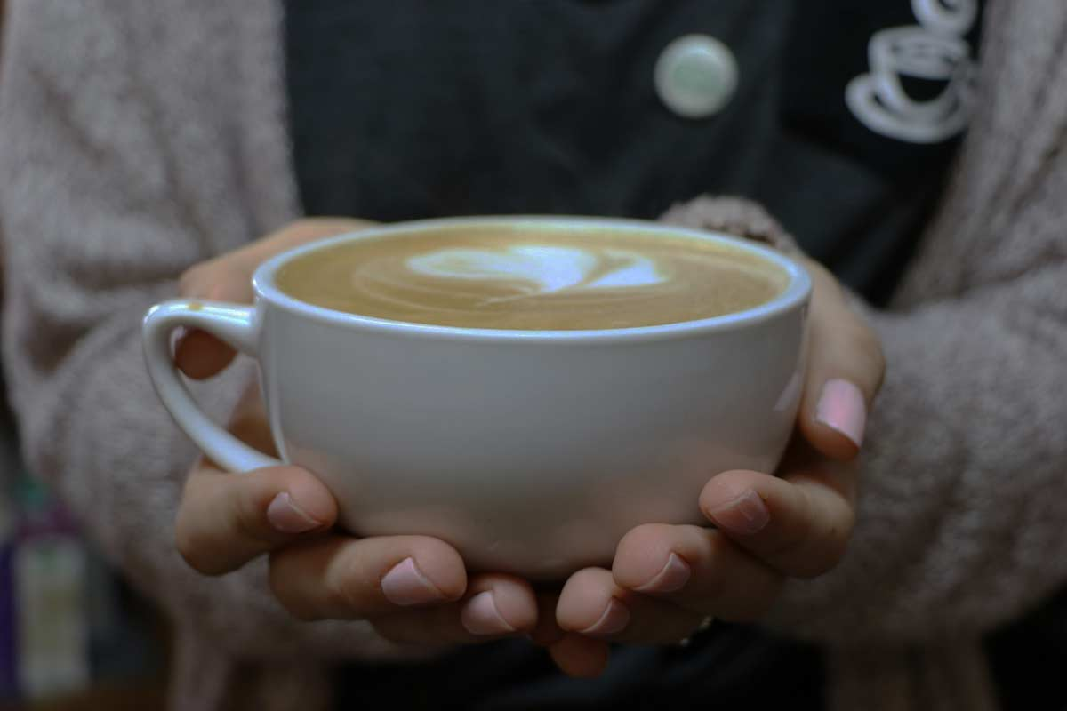 A Mochas & Javas barista holding a cappuccino topped with a heart-shaped foam