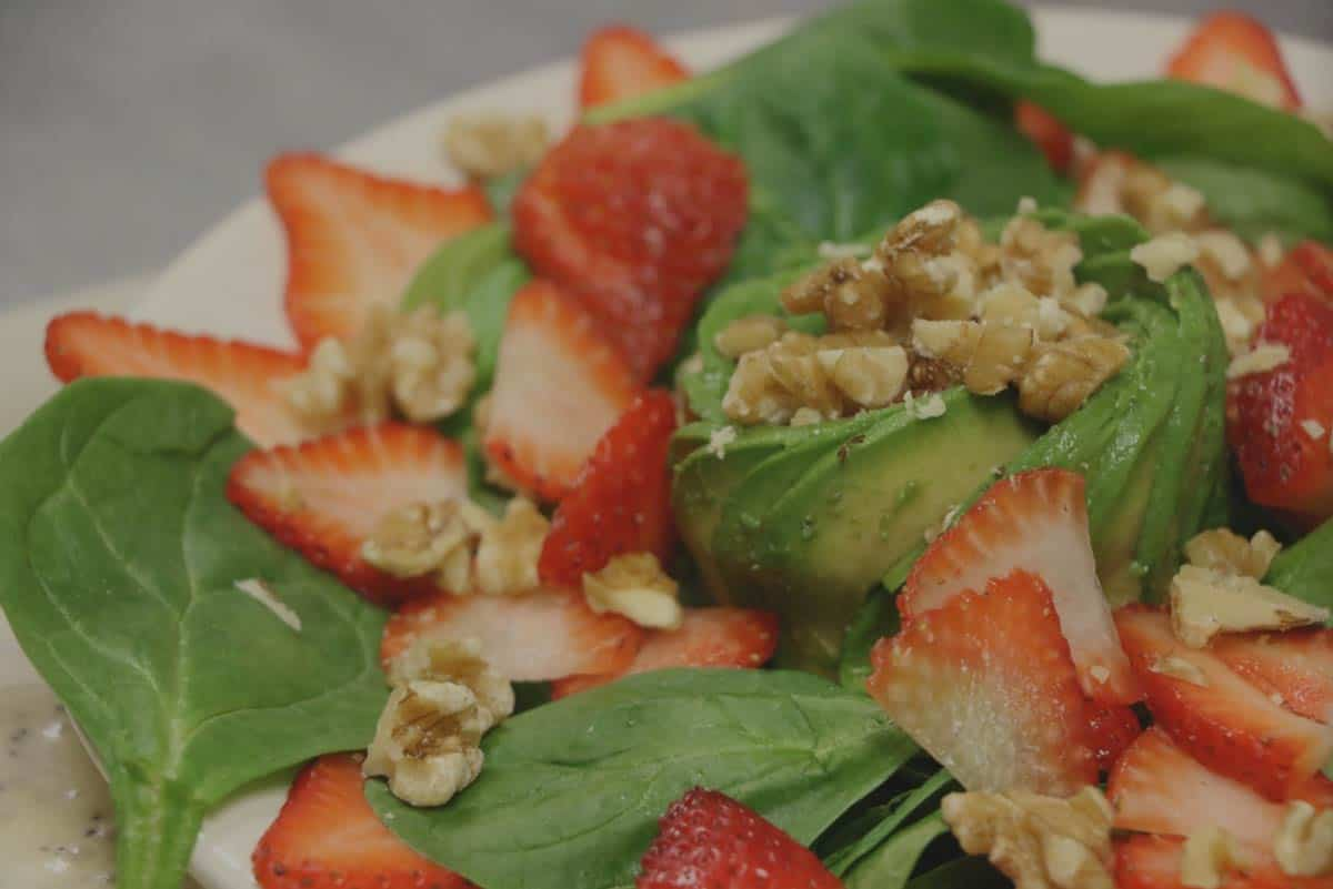 A vegan sweet & Tangy salad with strawberries, avocado, and walnuts