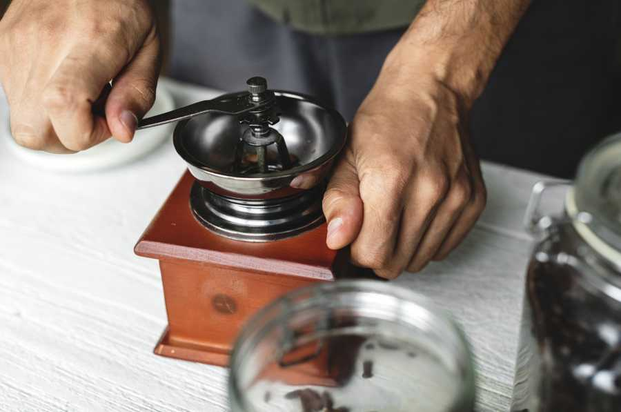 Person grinding coffee beans in small wooden traditional grinder