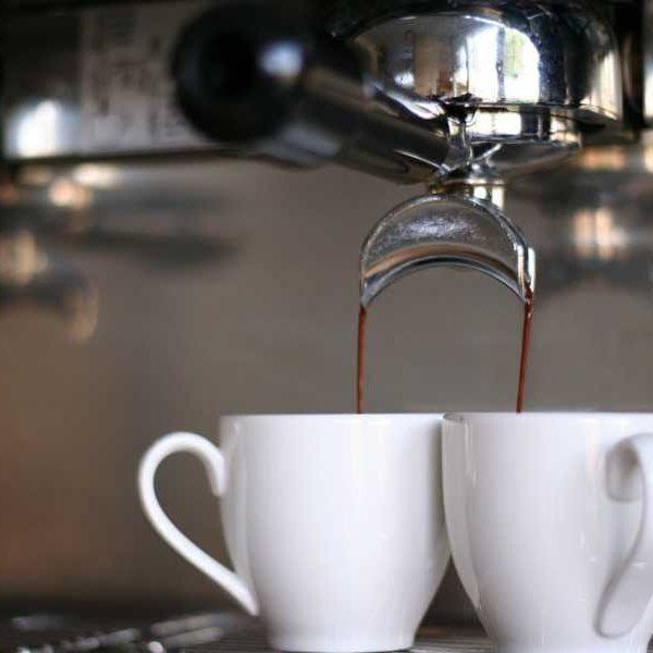 Mugs filled by espresso from espresso machine