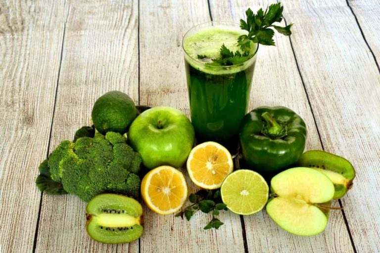A selection of vegetarian fruits and vegetables around a green smoothie