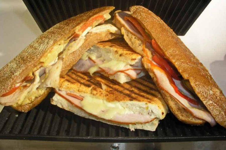 Two panini sandwiches cut in half and stacked on a grill