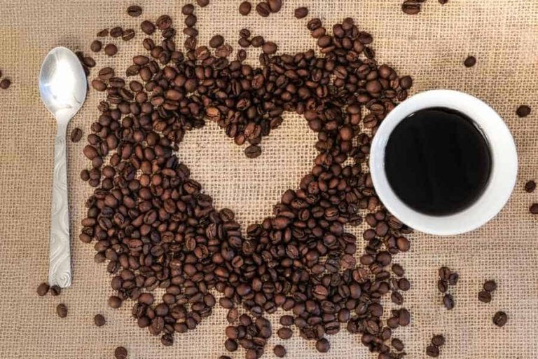 Coffee beans arranged around heart shaped negative space with cup and spoon beside
