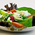 Fresh bowl of salad on white table