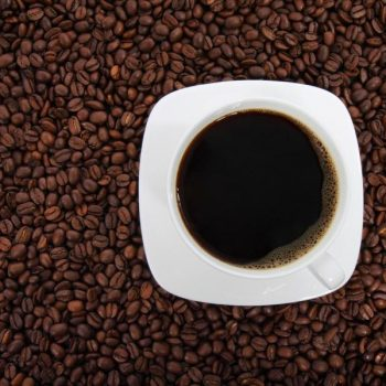 Cup of San Marcos coffee on background of coffee beans