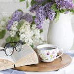 Cup of coffee on table with book and purple flowers
