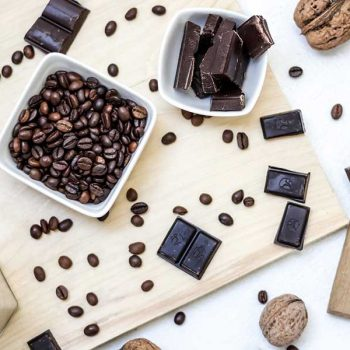 Coffee beans and chocolate bars on a cutting board