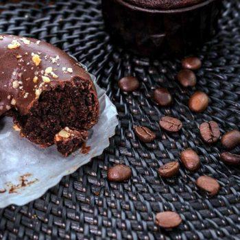Chocolate doughnut with a coffee glaze next to coffee beans