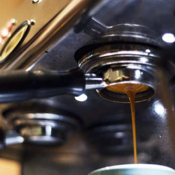 Close-up of a commercial espresso machine pulling a shot