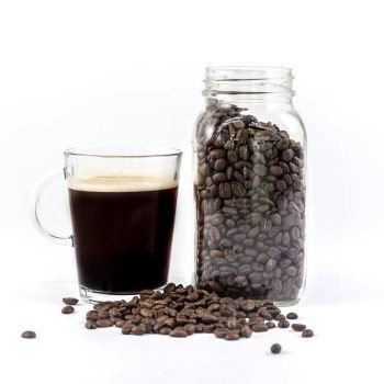 A mason jar of coffee beans next to a glass of freshly brewed coffee