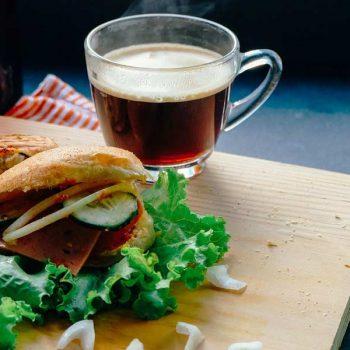 Cup of tea next to a veggie sandwich