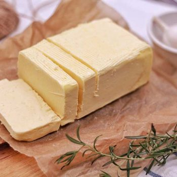 Sliced block of grass-fed butter next to garlic and herbs