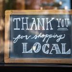 """A chalk board in a window with the words """"Thank you for shopping local"""" on it."""