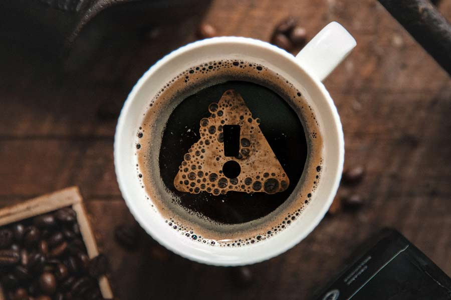 Cup of coffee with an exclamation mark made out of bubbles
