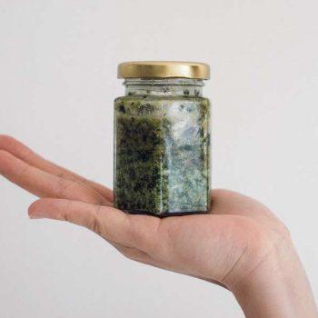 Hand presenting a jar of pesto
